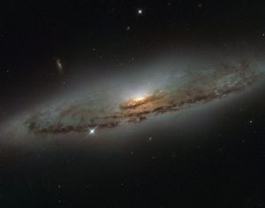 This NASA/ESA Hubble Space Telescope image shows the spiral galaxy NGC 4845, located over 65 million light-years away in the constellation of Virgo (The Virgin). The galaxy's orientation clearly reveals the galaxy's striking spiral structure: a flat and dust-mottled disc surrounding a bright galactic bulge. NGC 4845's glowing centre hosts a gigantic version of a black hole, known as a supermassive black hole. The presence of a black hole in a distant galaxy like NGC 4845 can be inferred from its effect on the galaxy's innermost stars; these stars experience a strong gravitational pull from the black hole and whizz around the galaxy's centre much faster than otherwise. From investigating the motion of these central stars, astronomers can estimate the mass of the central black hole — for NGC 4845 this is estimated to be hundreds of thousands times heavier than the Sun. This same technique was also used to discover the supermassive black hole at the centre of our own Milky Way — Sagittarius A* — which hits some four million times the mass of the Sun (potw1340a). The galactic core of NGC 4845 is not just supermassive, but also super-hungry. In 2013 researchers were observing another galaxy when they noticed a violent flare at the centre of NGC 4845. The flare came from the central black hole tearing up and feeding off an object many times more massive than Jupiter. A brown dwarf or a large planet simply strayed too close and was devoured by the hungry core of NGC 4845.